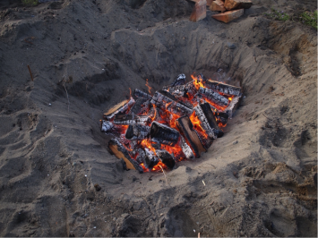 The fire warming the stones whose heat cooked the food in the pit-fire (photo – Robin Haig)